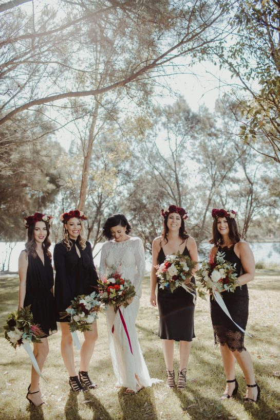 bridesmaids in black dresses and flower crowns